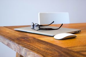 laptop with glasses on top and mouse on table